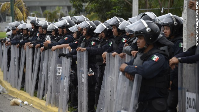 Riot police stand guard near the airport during clashes following a protest against the suspected massacre of 43 missing Mexican students, in Acapulco, in the Mexican state of Guerrero State, on November 10, 2014. Protesters angry at the suspected massacre threw stones and a firebomb at riot police in the Pacific resort of Acapulco on Monday, injuring 11 officers. Around 300 students, some wearing masks and armed with sticks and machetes, were joined by some parents of the 43 missing young men as they marched toward the city's airport, but police blocked their way. Mexico was confronted with one of the grisliest massacres in years of drug violence after gang suspects confessed to slaughtering 43 missing students and dumping their charcoaled remains in a river. AFP PHOTO/RONALDO SCHEMIDT        (Photo credit should read )