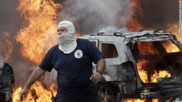 A firefighter is seen in front of vehicles set ablaze by protesters in Chilpancingo, Guerrero State, Mexico on November 12, 2014. Demonstrators angry over the disappearance of 43 college students set fire to the Guerrero state congress in southern Mexico on Wednesday in a new protest over the presumed massacre. AFP PHOTO/Pedro Pardo (Photo credit should read Pedro PARDO/AFP/Getty Images)