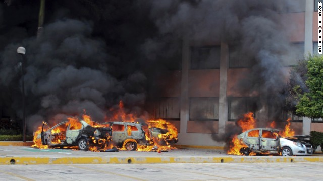 Cars burn in front of the state congress building after protesting teachers torched them in the state capital city of Chilpancingo, Mexico, Wednesday Nov. 12, 2014. Violent protests over the disappearance of 43 college students continue and are now threatening tourism in the nearby resort city of Acapulco ahead of a major holiday weekend when Mexicans traditionally flock to the beach, business leaders said Wednesday. Investigators say the 43 students from a rural teachers college were rounded up by local police, turned over to a drug gang and apparently killed, their corpses charred into ash and dumped into a river. (AP Photo/Alejandrino Gonzalez)