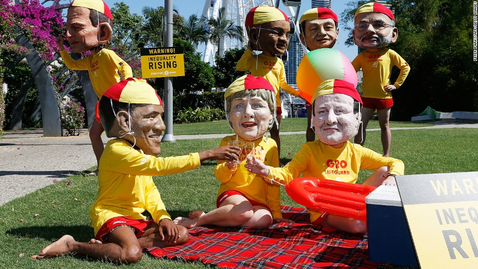 Protesters, wearing fiberglass heads depicting world leaders, pose in the park as they campaign for greater global equality during G20 in Brisbane.