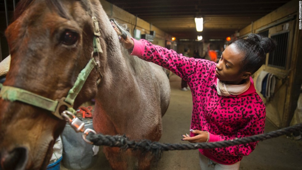 "A young program participant grooms her horse inside a stable at the equestrian center. ""We use horses as a hook to create pride, esteem and healing,"" Kelly said. ""They learn that they have ability. They just have to unlock it."""