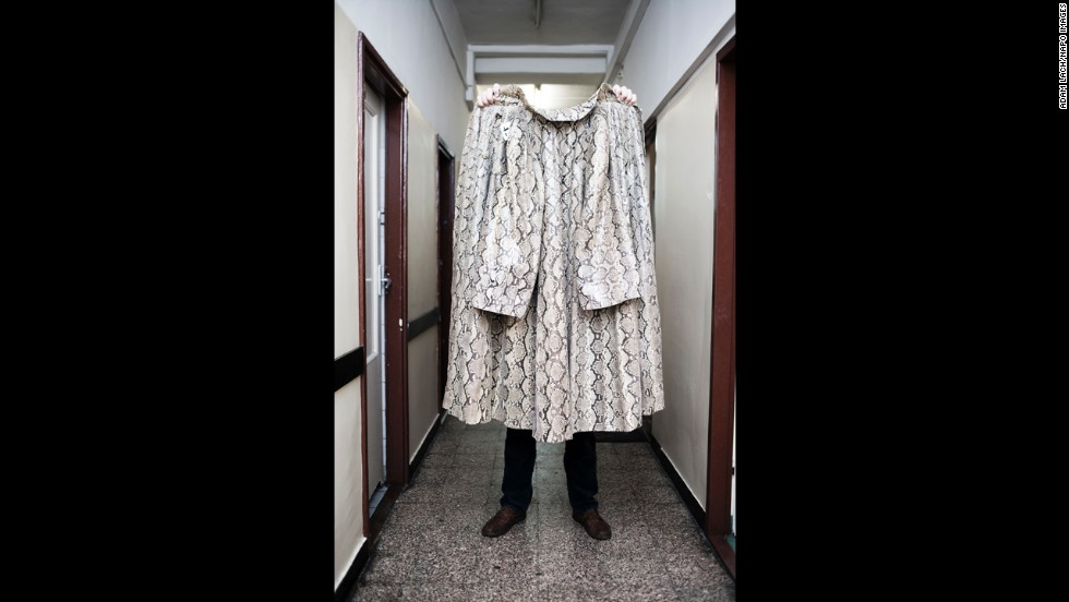 "A snake skin coat is held up in Warsaw. ""This project aims to show human arrogance and folly and to build in us humility,"" Lach said."