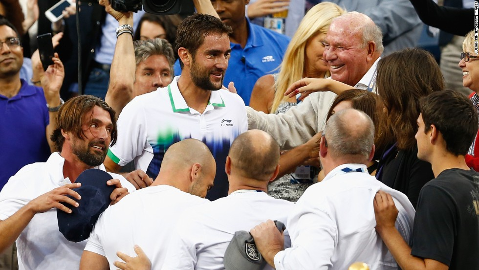 Cilic and a visibly-drained Ivanisevic celebrate with their support team following the world No. 9's first grand slam victory.