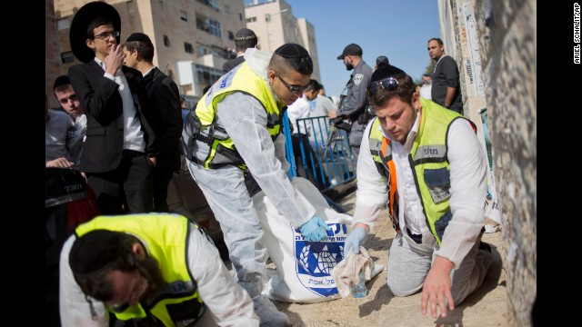 Response teams clean blood from the streets near the synagogue.