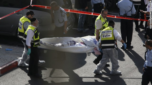 Israeli Zaka emergency services volunteers carry the body of one of the two Palestinian assailants who were shot dead while attacking a synagogue in the ultra-Orthodox Har Nof neighbourhood in Jerusalem on November 18, 2014. The attack, that killed four Israelis, began shortly before 7am (0500 GMT) as worshippers were attending morning prayers. AFP PHOTO / GALI TIBBON        (Photo credit should read GALI TIBBON/AFP/Getty Images)