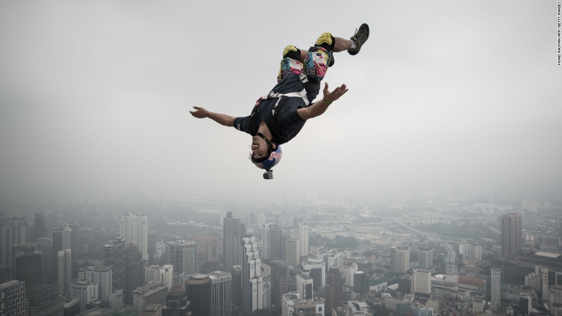 "A base jumper leaps from the 980-foot open deck of Malaysia's Kuala Lumpur Tower. <a href=""http://www.cnn.com/interactive/2014/11/specials/wish-you-were-here/index.html#basejump"">Base jumping</a> is an extreme sport in which participants leap from fixed objects and use parachutes to slow their falls."
