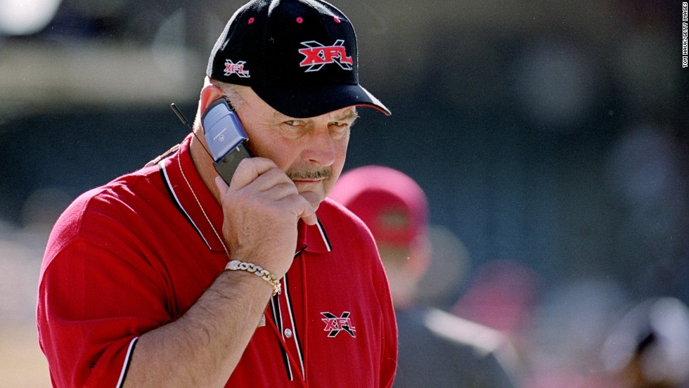 "Aside from flip phones, few things say ""early 2000s"" like the XFL. In this 2001 image, football legend Dick Butkus, the short-lived league's Director of Football Competition, growls (we're guessing) into his flip phone."