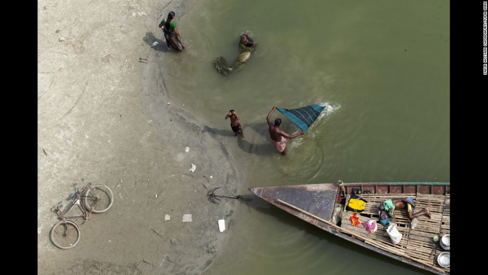 People in Dhaka, Bangladesh, spend time in a dried-up bed of the Kaliganga River on Monday, November 17.