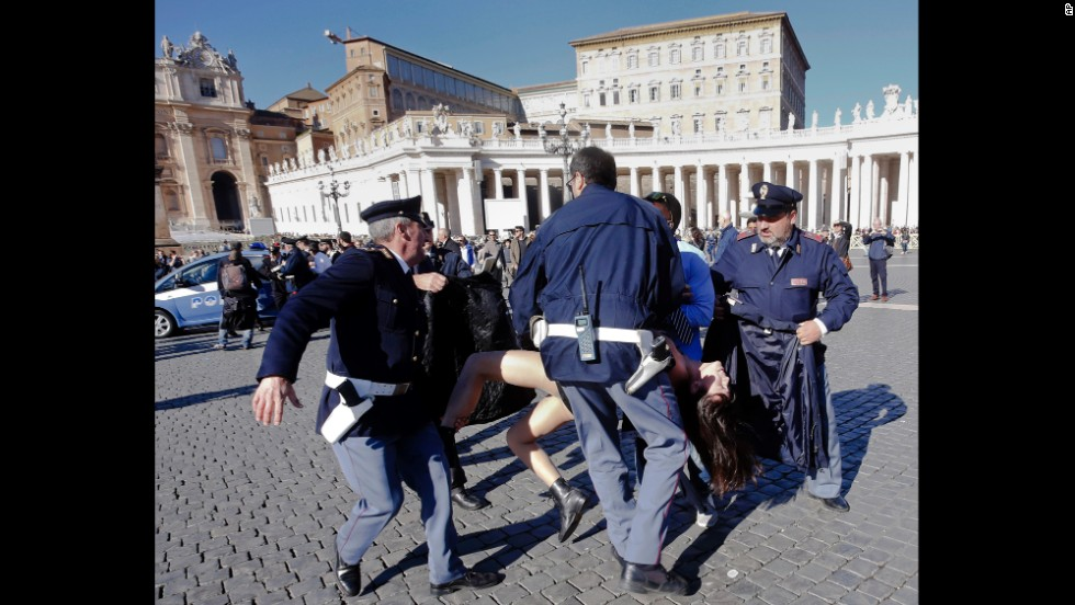 Police officers at the Vatican carry away an activist during a protest Friday, November 14, in St. Peter's Square. The Ukrainian feminist group Femen was protesting the Pope's upcoming visit to the European Parliament and Council.