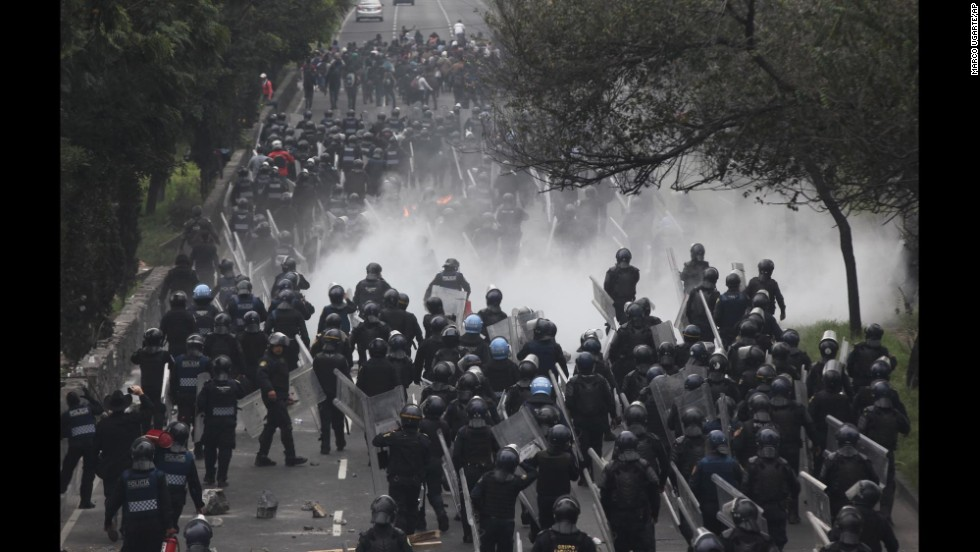 Riot police confront protesters near the airport in Mexico City on Thursday, November 20.