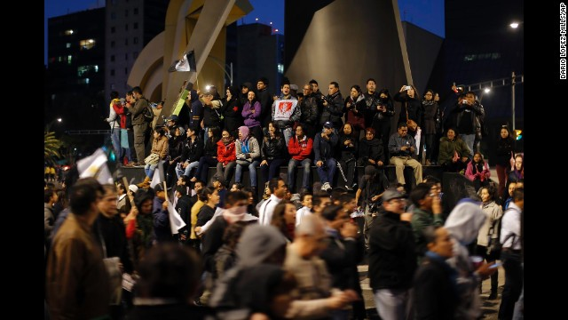 People on top of the base of a monument watch and cheer as protesters walk during a march in Mexico City.
