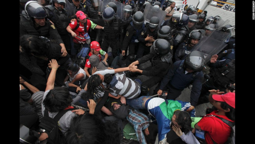 Riot police surround protesters who had thrown Molotov cocktails and destroyed vehicles in Mexico City on November 20.