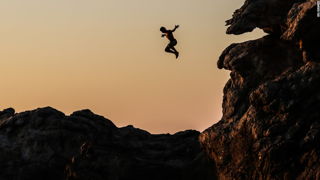 A cliff jumper plunges toward Artimus Cove in Ikaria, Greece.