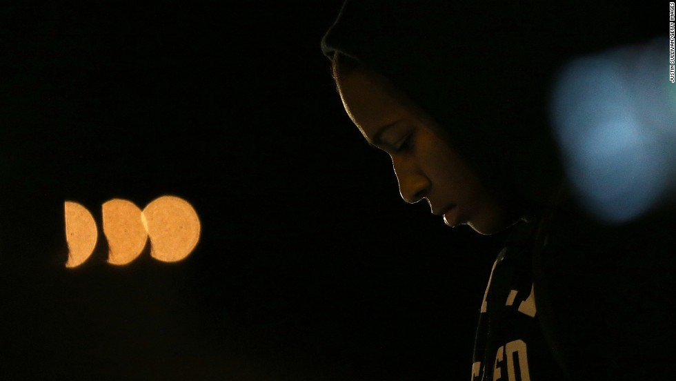 A demonstrator listens to a car radio as the grand jury's decision is delivered in front of the Ferguson Police Department.