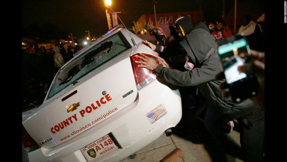 A group of protesters vandalizes a police vehicle in Ferguson on November 24.