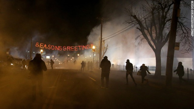 Protestors run away after police deployed tear gas during a demonstration in Ferguson, Missouri, on Monday, November 24.