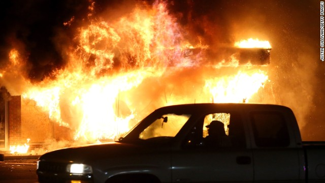 Caption:FERGUSON, MO - NOVEMBER 25: A car drives by a burning building during a demonstration on November 25, 2014 in Ferguson, Missouri. Ferguson has been struggling to return to normal after Brown, an 18-year-old black man, was killed by Darren Wilson, a white Ferguson police officer, on August 9. His death has sparked months of sometimes violent protests in Ferguson. A grand jury today declined to indict officer Wilson. (Photo by Justin Sullivan/Getty Images)