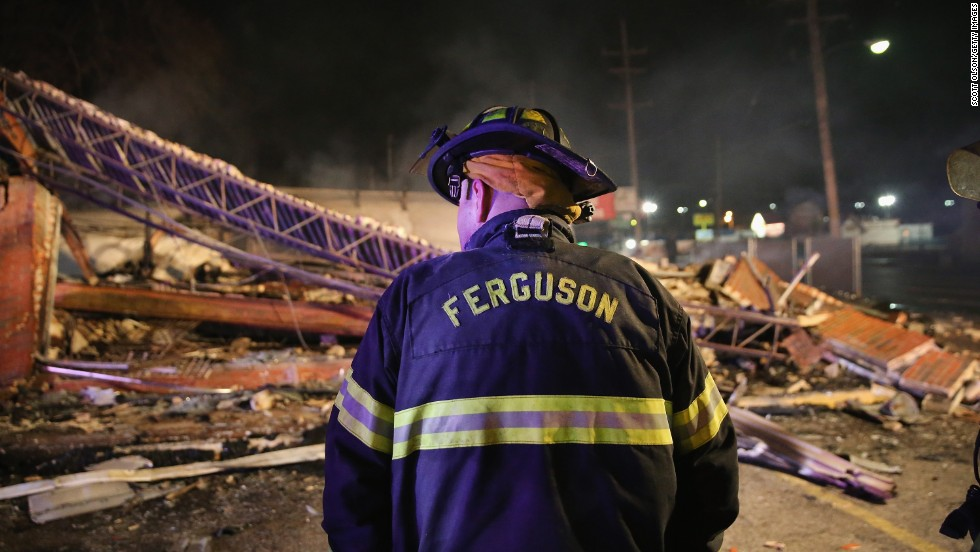 A Ferguson firefighter surveys rubble at a strip mall that was set on fire overnight.