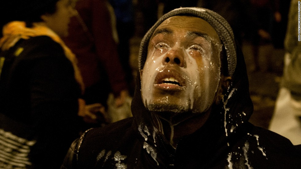A Seattle protester pours milk in his eyes after being tear-gassed on November 24.