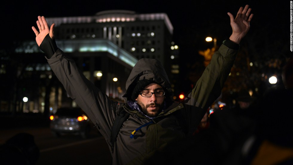 A protester in Denver holds up his arms during a moment of silence November 24 at Civic Center Park.
