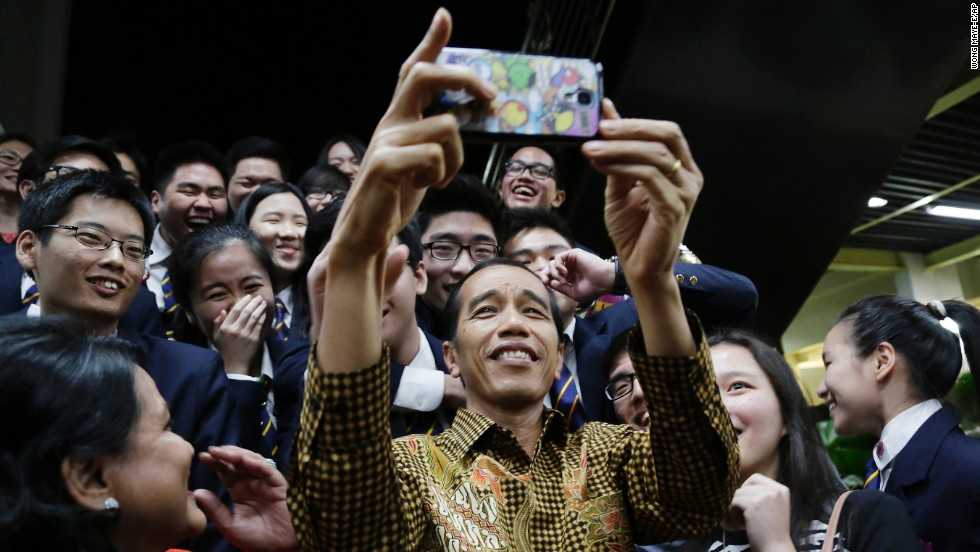 Indonesian President Joko Widodo takes a selfie with his son, top right, and other students after a graduation ceremony at the Anglo-Chinese School in Singapore on Friday, November 21.