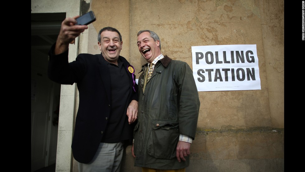 Nigel Farage, leader of the UK Independence Party, poses for a selfie with party worker Lee Jarvis, left, at a polling station in Rochester, England, on Thursday, November 20.