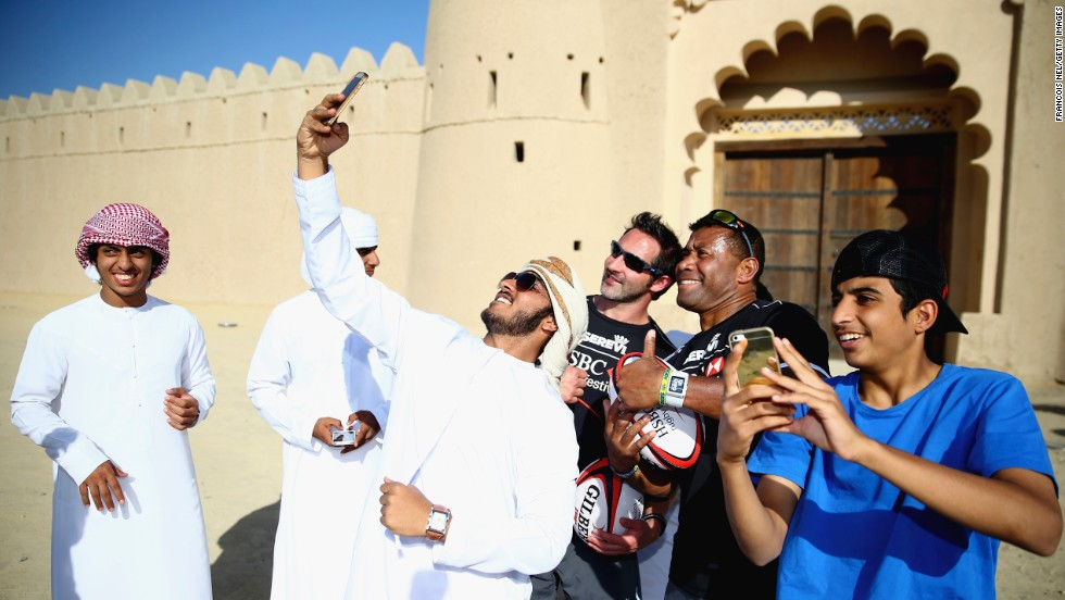 Schoolboys in Al Ain, United Arab Emirates, take selfies with rugby players Ben Gollings and Waisale Serevi during the HSBC Rugby Festival on Monday, November 24.