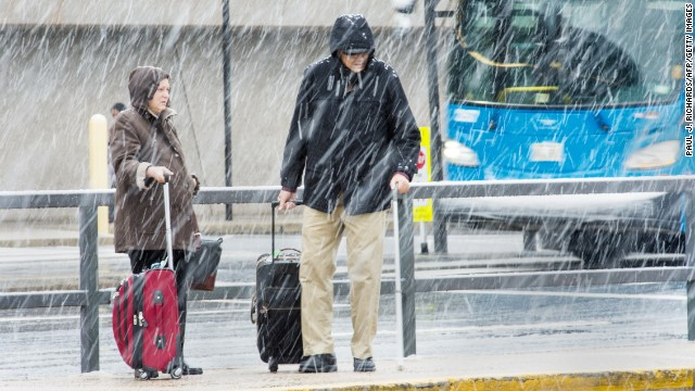 "Airline passengers at Dulles International Airport outside Washington, DC,  in Virginia, arrive to snow showers on the busiest travel day of the year November 26, 2014. Hundreds of flights were cancelled or delayed Wednesday in the US northeast as a winter storm delivered freezing rain and snow ahead of the Thanksgiving holiday, one of the year's biggest travel weekends. A wintry mix was falling in Boston, Philadelphia, New York and Washington, according to the National Weather Service, which forecast ""havoc"" for travelers along the east coast from the Carolinas up through New England.    AFP Photo/Paul J. Richards        (Photo credit should read PAUL J. RICHARDS/AFP/Getty Images)"