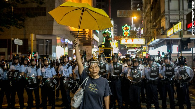 NOVEMBER 25 - HONG KONG: A pro-democracy activist holds a yellow umbrella in front of a police line on a street in Mong Kok district on November 25, 2014 in Hong Kong. Police and authorities have started clearing barricades and tents from the group's protest camp, almost two months after demonstrations began.