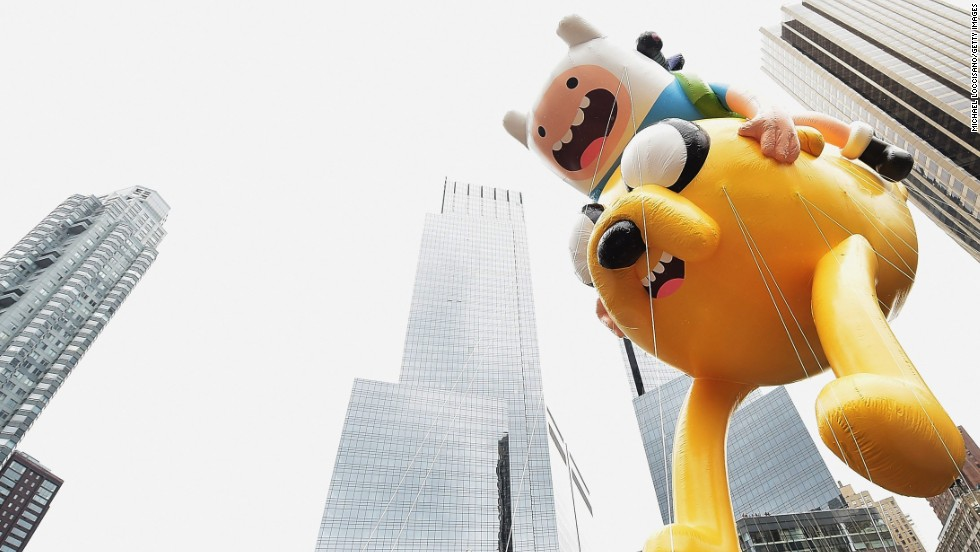 "The ""Adventure Time"" balloon passes by skyscrapers."