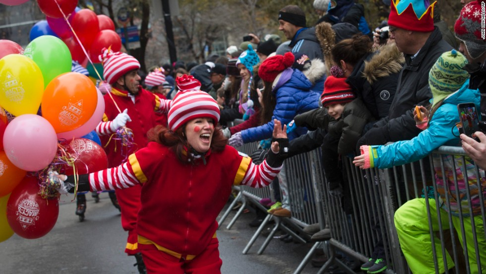 A performer waves and cheers as she skates past spectators.