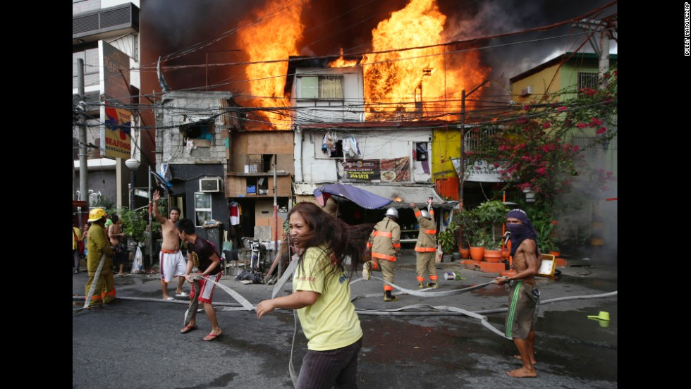 <strong>April 29:</strong> Residents help firefighters put out a blaze that engulfed a neighborhood in Manila, Philippines.