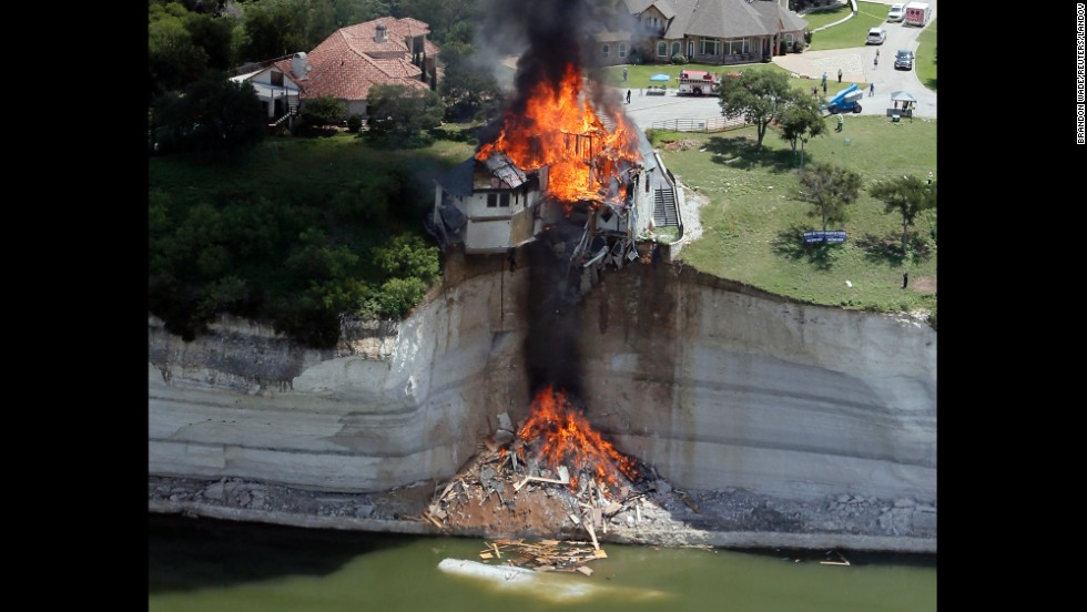 <strong>June 13:</strong> Smoke rises from a house that was deliberately set on fire by building crews near Lake Whitney in Texas. The house was set on fire after part of the ground underneath it collapsed into the lake.