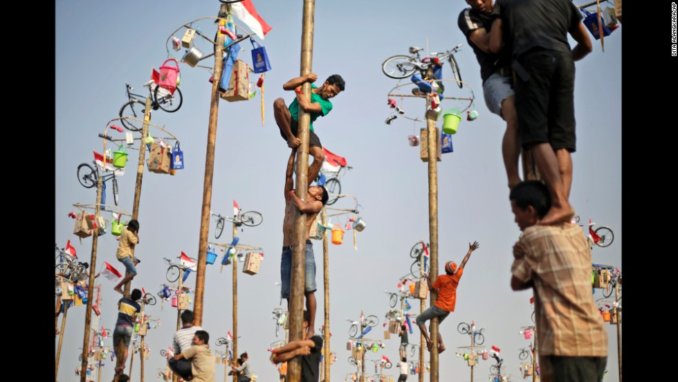 <strong>August 17:</strong> People in Jakarta, Indonesia, struggle to climb greased poles during a competition that was part of the country's Independence Day celebrations.