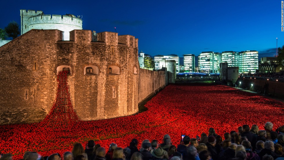"<strong>November 7:</strong> Visitors view <a href=""http://www.cnn.com/2014/08/04/europe/gallery/tower-of-london-art-installation/index.html"">the ceramic poppy installation</a> at the Tower of London. Thousands of ceramic poppies were installed in the dry moat surrounding the tower to mark the 100th anniversary of World War I. There were 888,246 poppies, one for each British military member that died during the war. The installation, called ""Blood Swept Lands and Seas of Red,"" was created by artist Paul Cummins."