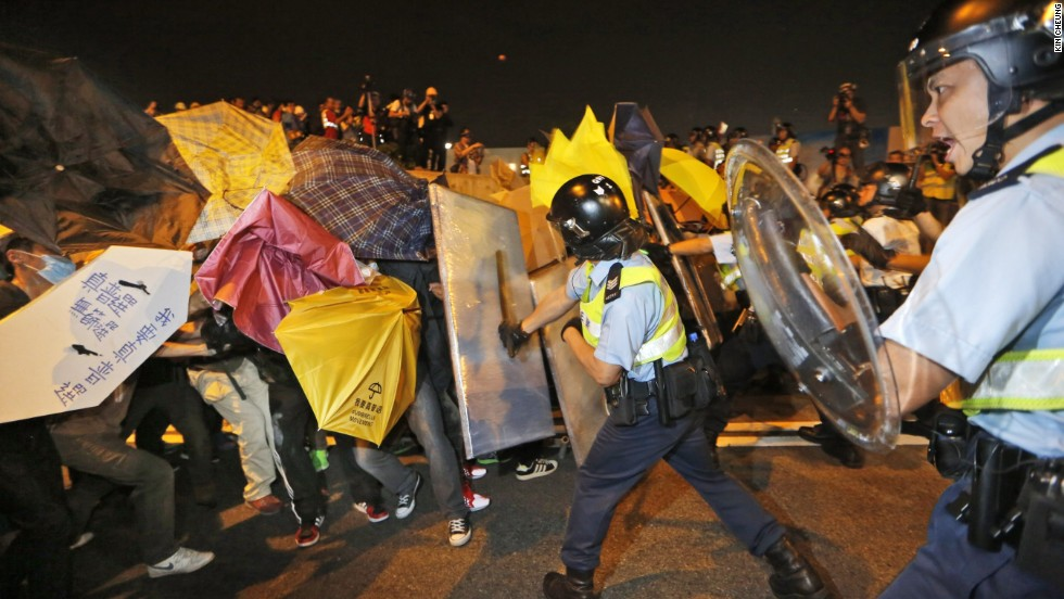 Pro-democracy protesters collide with police officers on the main road outside the government headquarters in Hong Kong on November 30.