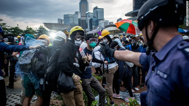 HONG KONG - DECEMBER 01: Pro-democracy protesters clash with police outside Hong Kong's Government complex on December 1, 2014 in Hong Kong. Leaders from the Federation of Students called on fellow protesters to attend a rally and come prepared for escalated action. Protesters were asked to bring masks, umbrellas and helmets in a bid to move the protests forward after police successfully cleared the Mong Kok protest site earlier this week. (Photo by Chris McGrath/Getty Images)