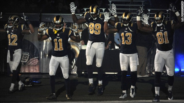 Members of the St. Louis Rams raise their arms as they walk onto the football field in St. Louis before their game against the Oakland Raiders  Sunday, November 30.