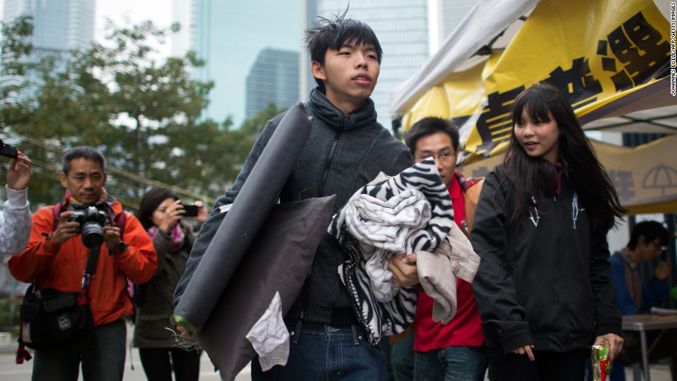 "Student protest leader <a href=""http://www.cnn.com/2014/12/01/world/asia/hong-kong-protest-joshua-wong-hunger-strike/"">Joshua Wong</a> carries his belongings toward a tent at the main protest site in Hong Kong's Admiralty district on Tuesday, December 2. Wong and two other student demonstrators have begun a hunger strike to demand discussions with Hong Kong's leaders over political reform for the city."