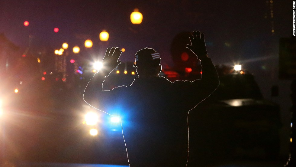 "A protester in Ferguson, Missouri, stands in front of police vehicles with his hands up on November 24, 2014. A grand jury's decision not to indict police Officer Darren Wilson in the killing of Michael Brown prompted<a href=""http://www.cnn.com/2014/11/24/justice/gallery/ferguson-reaction/index.html""> waves of protests in Ferguson</a> and across the country. The ""hands up, don't shoot"" gesture became a rallying cry and protest symbol."