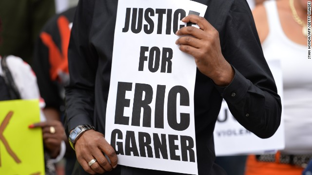 Caption:Demonstrators rally against police brutality in memory of Eric Garner on August 23, 2014 in Staten Island, New York. The New York City medical examiner's office ruled that Garner, the 43-year-old father of six, died from a chokehold and chest compressions while being arrested by the police on July 17, 2014. AFP PHOTO/Stan Honda (Photo credit should read STAN HONDA/AFP/Getty Images)