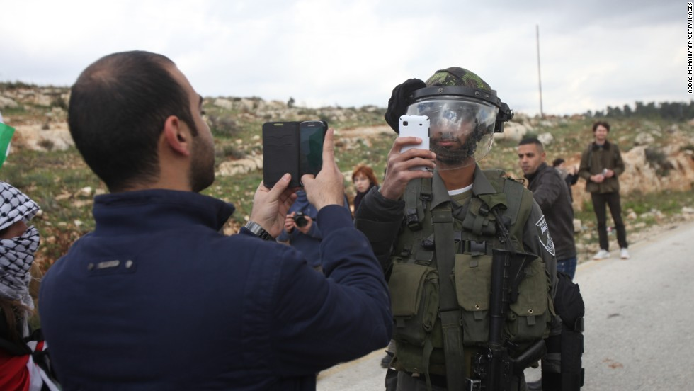 <strong>March 14:</strong> A Palestinian man and a member of Israel's security forces take pictures of each other after a demonstration in the West Bank village of Nabi Saleh.
