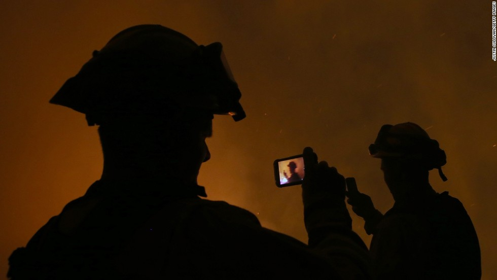 "<strong>September 17: </strong>Firefighters take pictures with their cell phones as they monitor a backfire in Fresh Pond, California. California Gov. Jerry Brown declared a state of emergency where <a href=""http://www.cnn.com/2014/09/18/us/gallery/california-oregon-wildfires/index.html"">wildfires torched tens of thousands of acres.</a>"