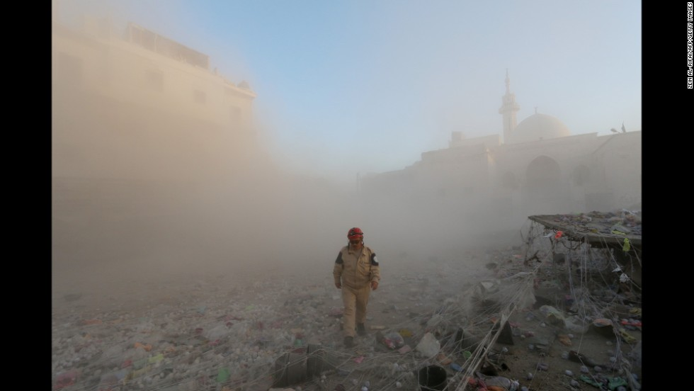 A member of the Syrian Civil Defense walks through a cloud of dust after an alleged air strike by government forces in Aleppo on November 11.