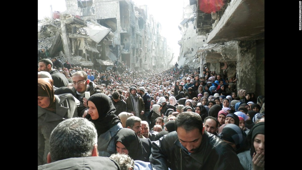 "<strong>January 31:</strong> Refugees at the besieged al-Yarmouk camp, south of Damascus, Syria, wait to receive food distributed by the U.N. Relief and Works Agency. Millions of people <a href=""http://www.cnn.com/2013/03/05/world/gallery/syrian-refugees/index.html"">have either fled Syria or become displaced</a> because of the civil war there."