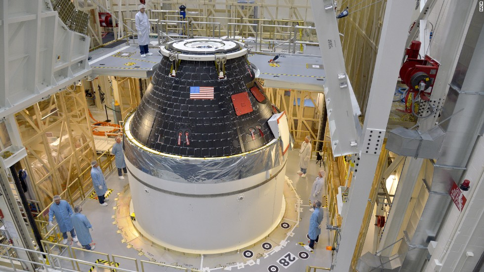 NASA's first completed Orion crew module sits atop its service module at Kennedy Space Center before being wrapped in protective panels and stacked on a Delta IV Heavy rocket for its first test flight.