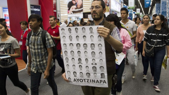 People take part in a protest for the 43 missing students at the International Book Fair in Guadalajara, Mexico, on December 3, 2014. AFP PHOTO/Hector GuerreroHECTOR GUERRERO/AFP/Getty Images