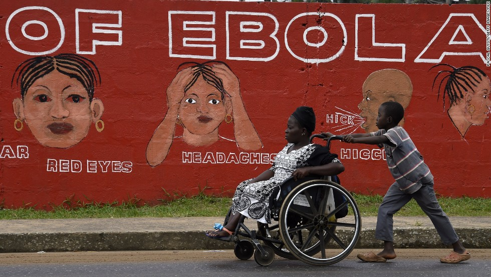 "A boy in Monrovia pushes a woman in a wheelchair past a wall bearing information about Ebola in September. Some villages lost their entire working-age populations, leaving countless orphans behind in their place. One nonprofit that works with orphans believes that <a href=""http://www.street-child.co.uk/ebola-orphan-report/"" target=""_blank"">more than 12,000 children</a> have lost their primary caregiver. Schools were shut down for almost a year and <a href=""http://www.savethechildren.org/site/c.8rKLIXMGIpI4E/b.9187887/k.9CB7/Helping_Children_Survive_the_Deadly_Ebola_Outbreak_in_Africa.htm?msource=weklpebo0814"" target=""_blank"">only recently reopened. </a>"