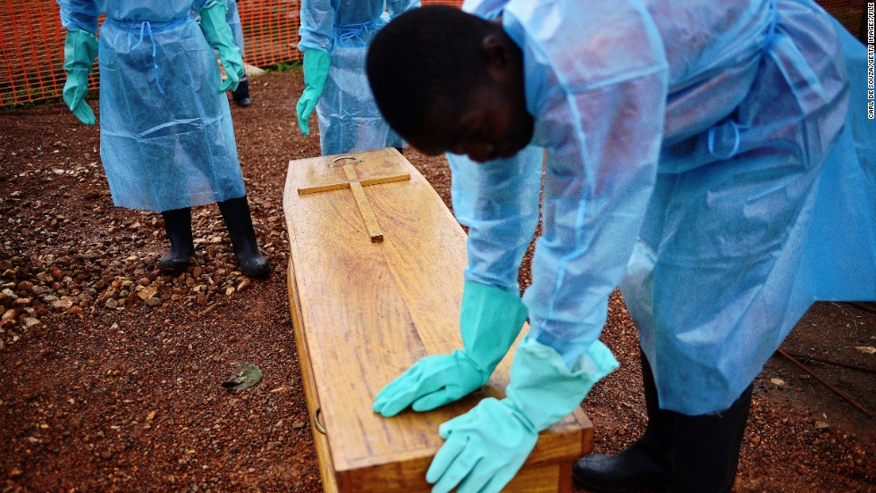 """I think one of the vital things we've failed to adhere to as a people, is not to touch a sick person,"" said Johansen of a disease in which <a href=""http://www.who.int/mediacentre/news/notes/2014/ebola-burial-protocol/en/"" target=""_blank"">20% of transmissions happen during burials.</a> Here, government burial team members wearing protective clothing stand next to the coffin of Dr Modupeh Cole -- Sierra Leone's second senior physician to die of Ebola."