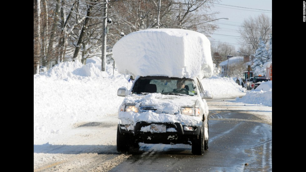 "<strong>November 19:</strong> A vehicle with a large chunk of snow on its roof drives along Route 20 after a massive snowfall in Lancaster, New York. <a href=""http://www.cnn.com/2014/11/19/us/gallery/wintry-weather/index.html"">A ferocious storm</a> dumped large piles of snow on parts of upstate New York, trapping residents in their homes and stranding motorists on roadways."